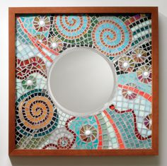 """""""Astral Reflections""""  Mosaic Mirror  Created by Carl Bryant, Sandra Bryant  Light sparkles in spirals and sunbursts of cut glass in this intricately designed, wood framed mosaic mirror. Each is unique and will vary slightly. Mirror glass is 7.5'' diameter.  Dimensions: 18.0in H x 18.0in W"""