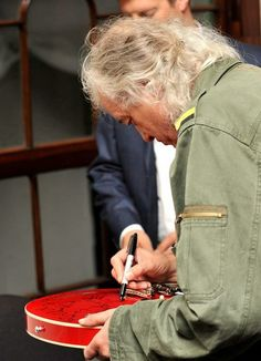 Jimmy Page autographing a guitar for a children's charity