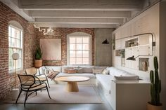 mix of brick, plaster, exposed beams, midcentury black lamp | design: jessica Helgerson via Remodelista