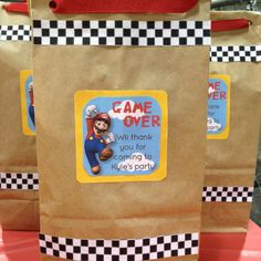 """Goodie bags for a """"Real Life Mario Kart"""" party at an indoor go kart place. Brown lunch bags, bought the personalized label image from etsy, printed checkerboard paper and glued it on as well.sealed with red ribbon. Go Kart Party, Race Party, Wii Party, Mario Kart, Mario Yoshi, Mario Bros., Mario And Luigi, Super Mario Party, Mario Party Games"""