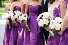 white bouquets popped on purple bridesmaid gowns! the bride carried all purple