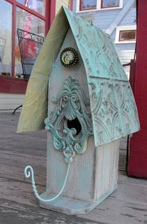 A Birdhouse Made Of Wood With A Tin Roof
