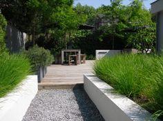 Vaste plantenbakken ter afscheiding van een grindpad.De strakke vormen en combinatie van hout en beton geven een moderne uitstraling
