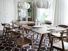Uma sala de reuniões com uma mesa comprida em chapa de nogueira e cadeiras com braços