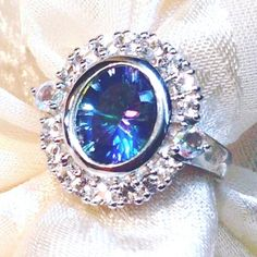 Petalite Halo Ring In Sterling Silver With White & Mystic Topaz, Handmade Jewelry By NorthCoastCottage Jewelry Design & Vintage Treasures. Here is a large, nearly 2CT flower petalite gemstone, 10x8 oval, set in sterling silver and circled by a halo of white topaz and accented by a