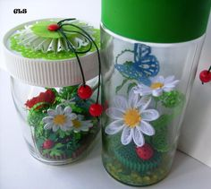 Glasses with quilled items displayed in them.