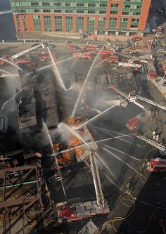 BOSTON MA  FIREFIGHTERS USE NUMEROUS AERIAL LADDERS AND HOSE LINES POUR MILLIONS OF GALLONS OF WATER ON THE JAMES HOOK LOBSTER COMPANY. MAY 30TH,2008. 7 ALARMS WERE USED TO GAIN CONTROL OF FIRE AN ESTIMATED 50,000 LBS OF LOBSTER WERE DESTROYED FROM THE FIRE. THIS IS A RARE AERIAL VIEW LOOKING DOWN ON SUCH A CHAOTIC SCENE.