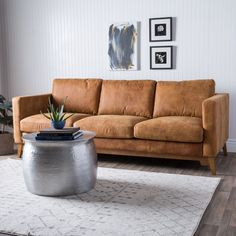 This handsome Filmore sofa features beautiful Italian leather upholstery with a semi-aniline finish in smooth tan. With a relaxed design and straight edges, this mid-century modern style chair is mounted on solid wood oak-finished feet.