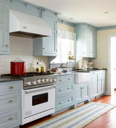 This cool kitchen is outfitted in gray-blue cabinets that are so pale they almost look neutral. Accented with soft yellow paint and a bright window over the farmhouse sink, this kitchen is full of cottage style. Intricate trim details at the top of the cabinets give them a built-in effect, and the hooked rug is another nod to the style./