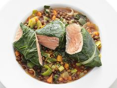 Salmon with Lentils ___________________ 1/4 cup extra-virgin olive oil, plus more for drizzling 2 leeks, white and light-green parts only, halved lengthwise and chopped 2 carrots, diced 3 cloves garlic, chopped 1 tablespoon tomato paste 1 cinnamon stick 1/2 pound (1 1/4 cups) French brown or green lentils 1 bunch Swiss chard 3 6-ounce center-cut skinless salmon fillets Kosher salt and freshly ground pepper 1 tablespoon honey Juice of 1 lemon