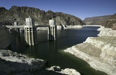 """A white """"bathtub ring"""" encircles Lake Mead near the intake towers of Hoover Dam as the lake fell to historic low levels on September 2004 near Boulder City, Nevada. (Photo by David McNew/Getty Images) Boulder City, Lake Mead, Hoover Dam, Towers, New Mexico, Bouldering, Nevada, Utah, Mount Rushmore"""
