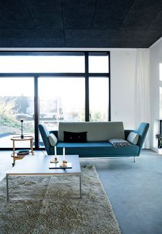 Open living room with a large window section and a 57-sofa which was designed by Finn Juhl and stands as a sculpture in the living room.