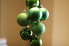 Easy Christmas centerpiece - hang ornaments from your dining room light fixture with fishing string.