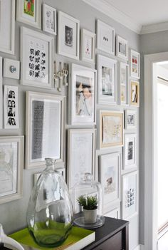 Collage wall to display pictures and other memorabilia. You can change out the pictures over time. Buy the same colored frames in a variety of styles and fill frames with anything meaningful, not just pictures. Basement entryway wall idea from Young House Love.