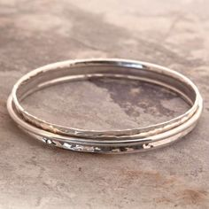 Cone Hammered Silver Bangle - In this Cone Hammered Silver Bangle a dazzling, gently hammered concave sterling silver band is encircled by a loose fitting silver ring - the resulting movement makes it impossible not to twiddle! #Otisjaxon #Jewellery