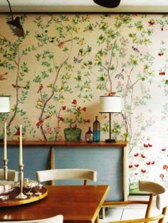 Re-upholster furniture in matching fabrics for further continuity- chances are that antiques and retro pieces will need a make-over anyway. Eclectic mid-century dining room with designer hand-painted wallpaper.