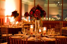 Corporate Holiday Party Decor - Wall lighting & warm candles with burgandy centerpieces