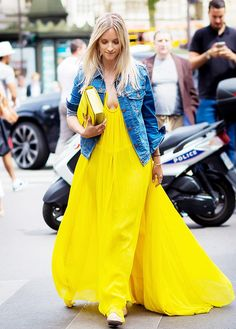 Blogger The Fashion Guitar wears a bright yellow maxi dress, matching bag, and denim jacket