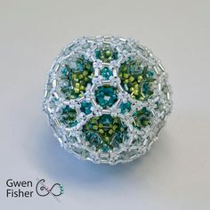 This large beaded bead is a composite of many different polygons and polyhera. The outside surface shows is rhombicosidodecahedron. I dont know how many beads are in it, but it weighs 14.5 grams, so Im sure it has more than 1000 beads.  The beads are all glass seed bead and bugle beads in