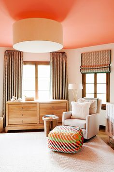 Salmon ceiling in nursery with patterned curtains and pouf, white rocking chair, and light wood dresser