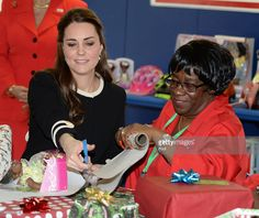 Catherine, Duchess of Cambridge helps to wrap Christmas presents during a visit to the Northside Center for Child Development on December 8, 2014 in New York City. The royal couple are on an official three-day visit to New York with Prince William also due to meet President Barack Obama in Washington D.C today.  (Photo by Mark Stewart - Pool/Getty Images)