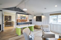 Game room boasts vaulted ceilings over board and batten trimmed walls which frame a large chalkboard lit by a pair of galvanized steel barn sconces over a pair of camel leather ottomans.