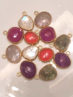 Love these - sapphires, rubies, fire opals and moonstones all set in 22k handcrafted bezel. One pair is better than the next