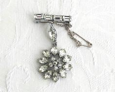 Vintage rhinestone brooch with dangling flower suspended from bar with 4…
