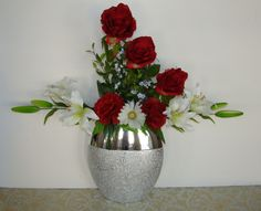 "This silk floral arrangement is a unique blend of artistry with the design of the arrangement and the distinctive pattern of the vase. The silk flowers include 3 premium red roses, 2 red carnations, 1 white daisy, 4 lilies with buds and ficus leaves and baby's breath. The glass vase is a combination of highly polished silver and a matte floral design silver. Total dimensions for this silk floral arrangement are 24"" high and 28"" wide."