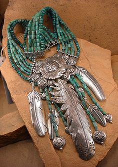 Necklace | Doug and Mary Hancock. Feathers, and Navajo beads  dangle from a textured silver Navajo button center with  multi-strand rondelle and rectangular Turquoise beads.