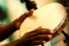 This instrument is called the Pandeiro.  It is from Brazil and it is a handheld frame drum with metal jingles attached.