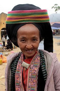 Dao Taipan woman at the marketplace of Niem Som.  The Dao (pronounced Zao) are the 9th largest ethnic group in Vietnam with a population of just under 500,000. They belong to the Hmong Dao language group and are believed to have started migrating from China in the 13th century. The women wear some of the most colourful and diverse costumes of all ethnic groups but can be identified by their black trousers richly embroidered with flower or small star patterns. Their jackets can be red or…