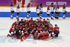 Feb 20, 2014; Sochi, RUSSIA; Team Canada celebrates winning the gold medal as team USA (who won silver) skates by in the background in the women's ice hockey gold medal game during the Sochi 2014 Olympic Winter Games at Bolshoy Ice Dome. Canada won 3-2 in overtime. (Winslow Townson-USA TODAY Sports)