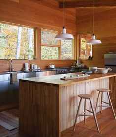 waterfall butcher block island + honed granite counters + stainless steel cabinets + warm wood detail in cottage of Suzanne Dimma via House & Home