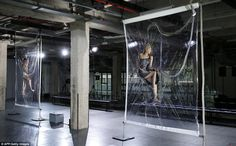 Iris van Herpen runway show with models suspended in vacuum sealed plastic before reveal of collection.