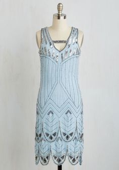 With festive occasions fast approaching, you turn to this icy-blue frock for glamour in a jiffy. Inspired by the decadent 1920s, this dazzling shift touts ornate beadwork, scalloped trim, and a sassy back cutout - for style that will match the band's quick tempo with electrifying elegance!