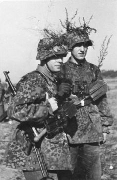 Waffen SS soldiers in camouflage uniform.  The one on the left packs a MP40 machine - pistole and 3 spare clips.