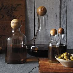 Gift idea for Fther's Day: Glass Bottles with Wood Stoppers. Sculptural spheres in natural wood function as stoppers for these shapely glass bottles, designed for decanting whiskey, wine, oil and vinegar. For a witty gift, monogram them with short words like 'sip,' 'refill' or 'enough.'