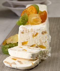 ΚΟΡΜΟΣ ΠΑΓΩΜΕΝΟΣ(ΣΕΜΙΦΡΕΝΤΟ) 180 γρ. ζάχαρη 6 κρόκοι αυγών 1 κιλό κρέμα γάλακτος με 35%-36% λιπαρά, χτυπημένη στο μίξερ με το σύρμα, μέχρι να γίνει παχύρρευστη σαν γιαούρτι 200 γρ. γλασαρισμένα φρούτα + επιπλέον για γαρνίρισμα 150 γρ. αμύγδαλα, με ή χωρίς το φλοιό 100 γρ. μπισκότα πτι-μπερ, κομμένα σε μικρά κομμάτια