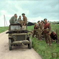 Invasion of Normandy 6 June 1944 Commandos of 1st Special Service Brigade with captured Germans in a jeep, with gliders of 6th Airlanding Brigade in the background, near Ranville, on the evening of 6 June 1944.