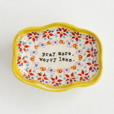 Dimensions: 2.88 x 2.25 x 1.13 Vintage-inspired small artisan trinket dish with yellow scalloped edge, red and pink flower border, and 'Pray More Worry Less' in typewriter font. Great as a ring dish!