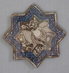 Star-Shaped Tile    Object Name:      Star-shaped tile  Date:      ca. 1300  Geography:      Iran, Kashan  Medium:      Stonepaste; overglaze luster-painted  Dimensions:      4 3/8 in. (11.1 cm)  Classification:      Ceramics