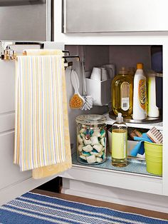 Clear Out Under the Sink A few clever, practical storage pieces can help you declutter your under-sink spot in the kitchen. Remove everything first, and add an elevated shelf to take advantage of the space's height. Put cleaning-solution bottles in a caddy (to better cart them from room to room) or on a lazy Susan. Hooks and additional trays keep other cleaning necessities in easy view.