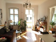 Wunderschönes lichtdurchflutets Wohnzimmer mit Balkonzugang, Couch, Highboard und großen Fenstern in Berlin. #Zwischenmiete #Kreuzberg #3Zimmerwohnung