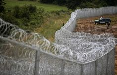 Bulgarian border police stand near a barbed wire fence on the Bulgarian-Turkish border July 17TH  2014. (Brussels) – Bulgarian border police have in the past month forced Syrian asylum seekers back to Turkey and beaten some of them, Human Rights Watch said today based on accounts by victims