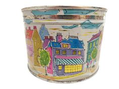 Wonderful lithographed tin from 1959 features a charming street scene in bright, happy colors. The tin is in very good vintage condition with minimal surface wear/rust, and one small bump on the lid which may actually be part of its original design, though Im not sure. The Mrs. Lelands candy tins came in many bright, engaging designs and are so much fun and relatively inexpensive to collect! Measures 5 in diameter and 3 1/2 tall.  I have another Mrs. Lelands candy tin in a separate listing…