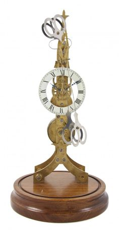 An English Brass Skeleton Clock, having a circular enameled chapter ring with Roman hours, having time only movement, set on a circular wood base.