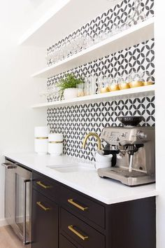 White floating shelves are fixed to black and white backsplash tiles over a sink with an antique brass gooseneck faucet fixed to a white quartz countertop beside an espresso machine.