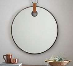 A small leather strap and decorative loop give this mirror its equestrian feel. The beveled glass is rimmed with a thin bronze-finished frame for understated elegance. Large Round Mirror, Round Mirrors, Diy Hanging Shelves, Guest Bathrooms, Bathroom Ideas, Cool Mirrors, Beveled Glass, Wall Art Designs, Houses