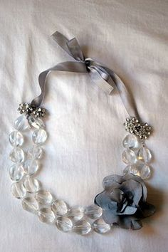 Super cute!   DIY - Fold a necklace in half.  Attach ribbon to both ends. Add clip earrings to hide the ribbon knots.  Add flower pin if desired.